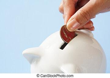 Money saving - A woman saving a coin into a piggy bank