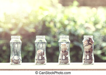 Stacked coins in 4 step growing on wooden table with nature background.