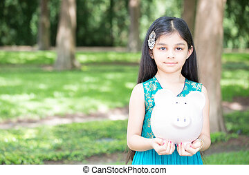 Money savings - Closeup portrait, young lady holding piggy...