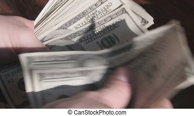 Hands shuffling through a stack of one hundred dollar bills (these are real bills totalling $9,000)