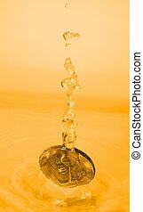 money splash - A euro coin drops into a gold liquid