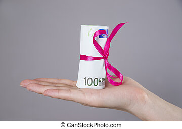 Money with ribbon in female hand on a gray background