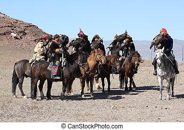 "MONGOLIA - 25 JULY: Senior Mongolians horsemen in traditional clothing with golden eagles during the festival of name ""The Golden Eagle Festival"" July 25, 2011, Mongolia - desert"