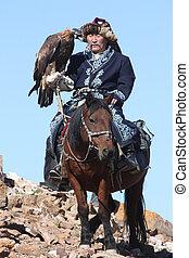 "MONGOLIA - 25 JULY: The senior Mongolian horseman in traditional clothing with golden eagles during the festival of name ""The Golden Eagle Festival"" July 25, 2011, Mongolia - desert"