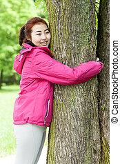 Mongolian girl hugging a tree