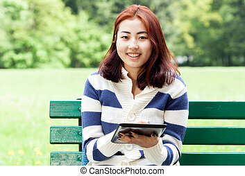 Mongolian woman sitting on a bench