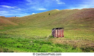 Mongolian wooden squat toilet outside home, grassland of...