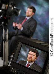 Monitor in studio showing man talking to video camera -...
