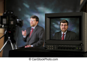 Monitor in TV production studio showing man talking to a...