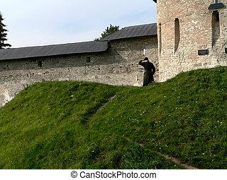 Monk beside conventual wall