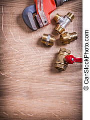 monkey wrench and brass plumbing fixtures  on wooden board with