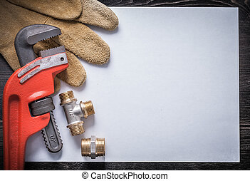 Monkey wrench brass plumbing fittings leather safety gloves clean paper.