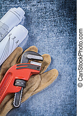 Monkey wrench rolled blueprints protective gloves on...