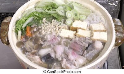 Monkfish pot during cooking with tohu and various...