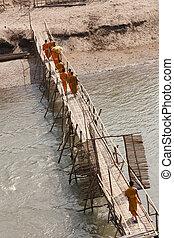 Monks over rickety bridge - Novice Buddhist monks cross a ...