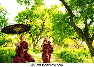 Monks - Two little Buddhist monks running outdoors under...