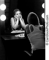 Monochorme portrait of sad woman looking at reflection in mirror