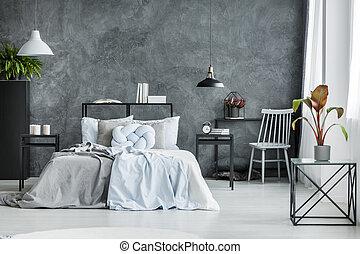 Monochromatic bedroom interior with plant