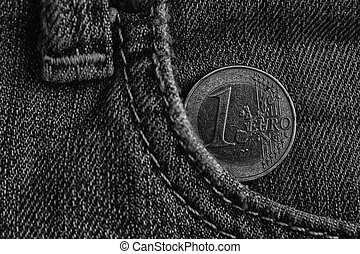 Monochrome Euro coin with a denomination of 1 euro in the pocket of blue denim jeans.