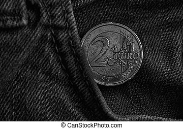 Monochrome Euro coin with a denomination of two euro in the pocket of old vintage blue denim jeans
