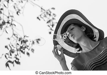 Monochrome image of a woman with hat blowing bubbles