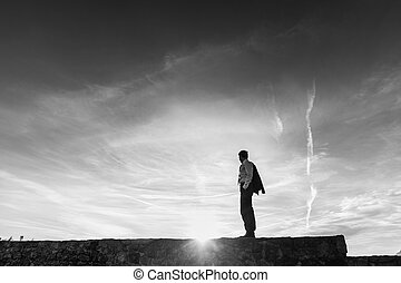 Monochrome image of business man standing on the skyline