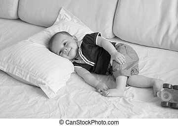 Monochrome image of cute 1 year old baby boy relaxing on big pillow