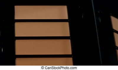Monochrome minimalistic palette of concealers - cosmetics for eliminating skin imperfections rotates on black mirrored background. Beauty, make-up, artist instruments concept. High quality 4k footage