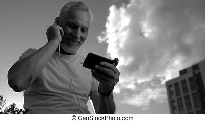 Monochrome of a positive senior man talking via the Internet...