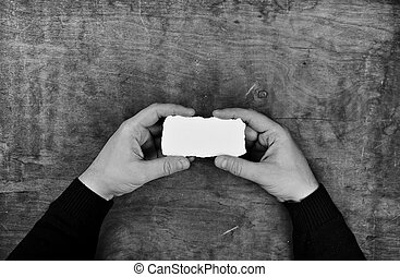 monochrome photo male hands holding a white blank sheet of paper