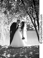 Monochrome photo of beautiful bride and groom kissing under big