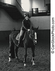 Monochrome photo of beautiful woman riding horse in manege