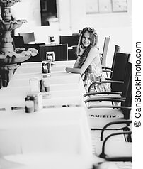 Monochrome photo of cute woman sitting at table in cafe