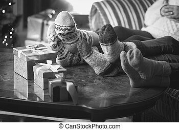 Monochrome photo of family warming feet at fireplace