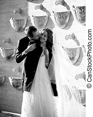 Monochrome photo of groom covering bride with jacket