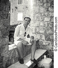 Monochrome photo of handsome man sitting on old street