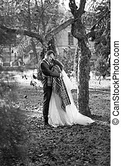 Monochrome photo of happy bride and groom hugging under tree