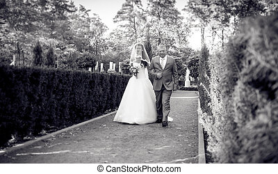 Monochrome photo of happy bride walking with father at park...