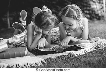 Monochrome photo of young girls looking at family photo ...