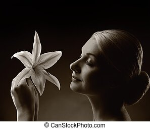 Monochrome picture of a beautiful woman with lily flower