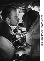portrait of bride and groom kissing in car