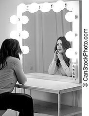 Monochrome portrait of brunette woman looking at reflection in mirror with light bulbs