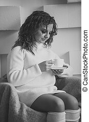 Monochrome portrait of cute woman in sweater looking at cup of tea