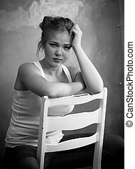 Monochrome portrait of cute young woman leaning on wooden chair