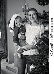 Monochrome portrait of happy mother and baby boy decorating Christmas tree