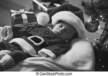 Monochrome portrait of sleeping baby boy in Santa costume