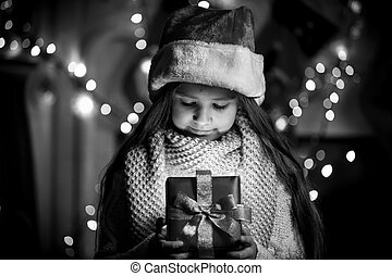 Monochrome portrait of smiling girl opening Christmas...