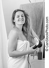 Monochrome portrait of smiling young woman drying long hair at bathroom mirror