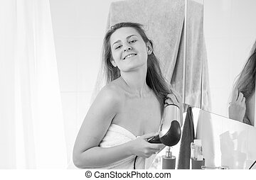 Monochrome portrait of young woman drying hair after having shower