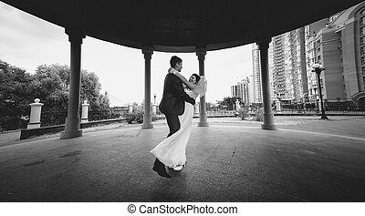 monochrome shot of bride and groom dancing at alcove in park...
